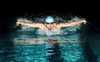 Man in swimming pool. Butterfly swimming style