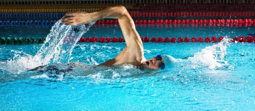 Man in swimming pool. Crawl swimming style