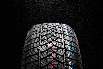 Winter Car tire on black background and rain
