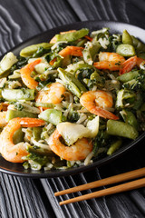 Stir fry of shrimp with spinach, soy sprouts, pea pods and  pak choi close-up. vertical