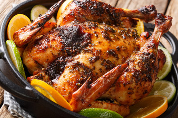Whole baked Cuban chicken marinated with mojo sauce served with oranges and lime close-up in a pan. horizontal