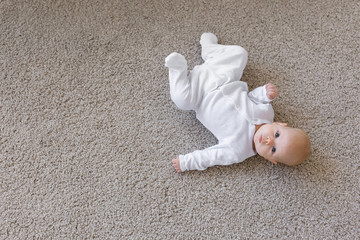 Baby, infant and childhood concept - Top view of the child on the floor with copy space