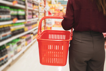 Cropped of young woman with basket in supermarket