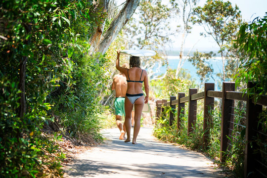 A woman walking carrying her longboard surfboard in Noosa National Park on the Sunshine Coast in Queensland