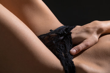 Sexy nude girl, stripper. Playful hand touching black panties. Classic nude. Sexy woman lying front of classic black studio background. Sensual girl in ecstasy, orgasm. Nude women in erotic pose.
