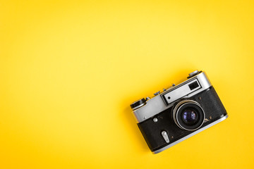 Old camera on yellow background.