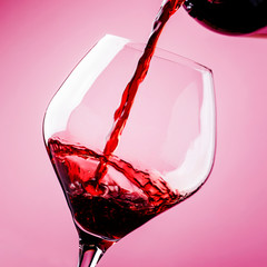 Dry red wine, pour in glass, pink background, defocused in motion image, shallow depth of field