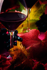 Semi-sweet red wine in large glasses, autumn still life with red and yellow leaves on pink background, selective focus