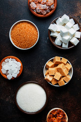 Set of different white and brown sugar in assortment, dark background, top view