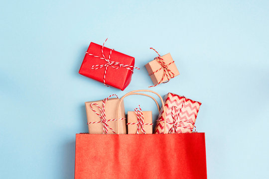 Red shopping bag with gifts on a blue background.