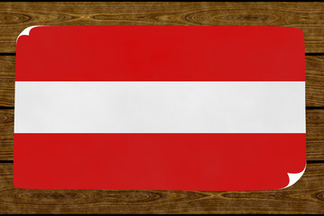Illustration of an Austrian flag on the paper pasted on the woody wall