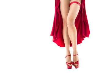 Slim long female legs in red dress and red high heeled shoes. Garter on her leg. sexy christmas