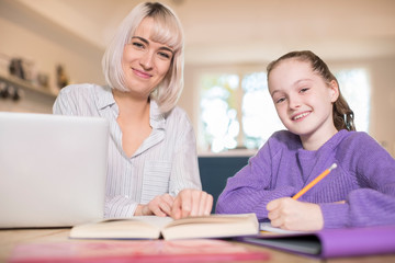 Portrait Of Female Home Tutor Helping Young Girl With Studies
