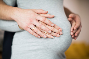 Close Up Of Male And Female Hands Resting On Pregnant Womans Stomach