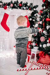 Christmas portrait of a young boy cozy atmosphere around the fireplace and Christmas tree