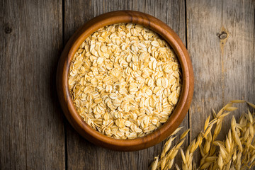 Wooden bowl with uncooked oats on the rustic wooden background. Selective focus. Shallow depth of field.