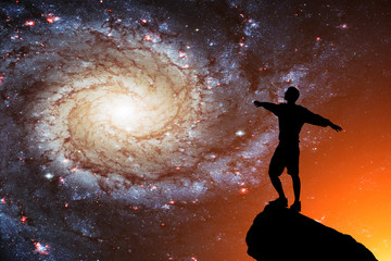 Silhouette of a lonely man against the background of the galaxy. Success concept