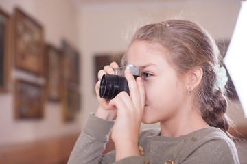 Girl with a retro camera makes a photo.