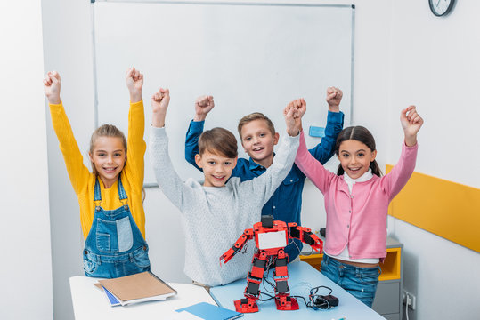 happy schoolchildren raising hands, smiling and looking at camera in stem class