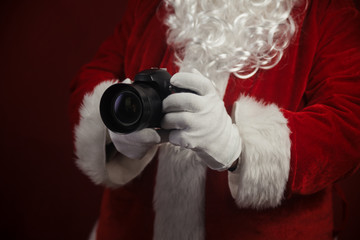 Santa Claus using holding in hands DSLR camera. Christmas and New Year celebration background.