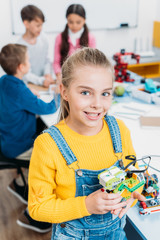 preteen schoolgirl holding multicolored robot and looking at camera in classroom