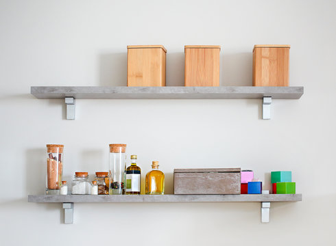 Arranged jars with various spices on kitchen shelves