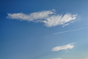 Clouds in the sky and an aeroplane smoke line. Smoke line in the blue sky. Clouds in the sky.