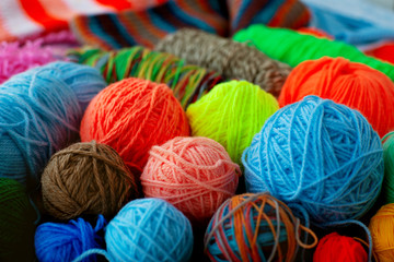 Many multicolored balls of yarn. Yarn for knitting of different colors and types. A lot of balls of yarn collected a bunch. Knitting as a kind of needlework.