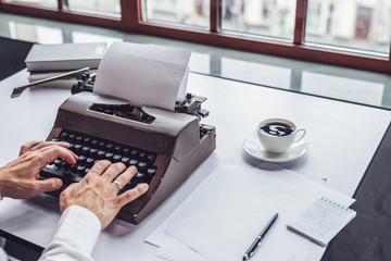Men's hands typing on a retro typewriter