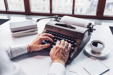 Young writer typing on a retro typewriter