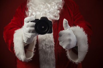 Santa Claus using DSLR camera taking images showing thumb up. Happy Christmas Evening and New Year celebration background. Fun loving creative costume time.