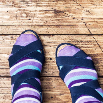 Women's feet in socks and sandals on wooden background.