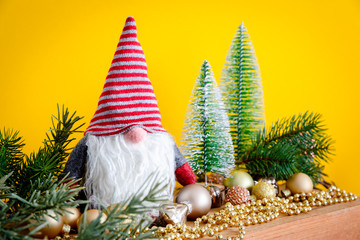 Christmas decoration with a gnome on a wooden box and yellow background