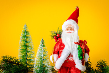 Santa Claus figure with fir trees on yellow background