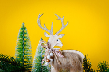 Christmas decoration wooden reindeer with fir trees on yellow background
