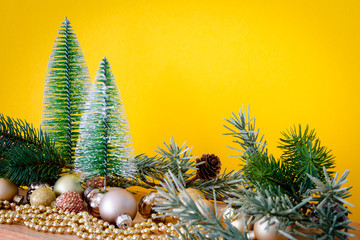 Christmas decoration glass balls with fir trees on yellow background