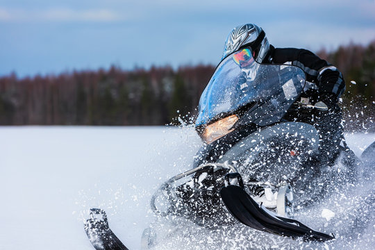 In deep snowdrift snowmobile rider driving fast. Riding with fun in white snow powder during backcountry tour. Extreme sport adventure, outdoor activity during winter holiday on ski mountain resort.