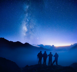 Group of travelers looking at the starry sky in the mountains.
