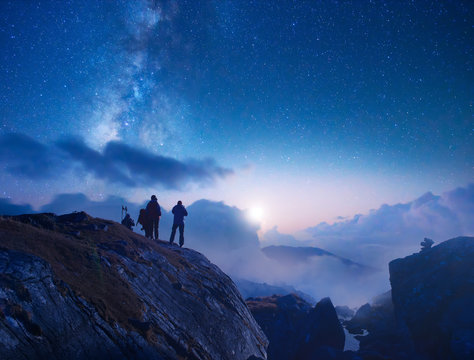 Group of travelers looking at the starry sky in the mountains