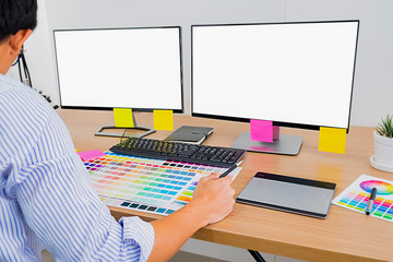 Graphic design with color swatches and tablet on a desk. Graphic designer drawing something on tablet at the office with work tools and accessories.