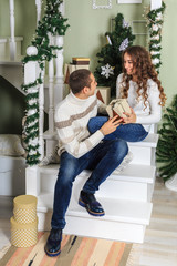 Young man and a young girl are sitting on the steps of a white staircase in a house in the eve of New Year holidays. The guy looking at the box with a gift