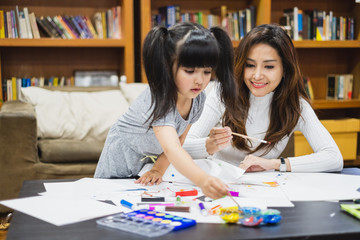 Asian girl kid and mother doing drawing with many colour pencils on white paper