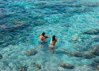 Happy couple swimming in the transparent turquoise sea.