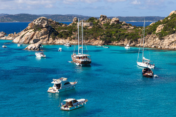 Yachts and boats in amazing azure sea water in Sardinia island, Italy Fototapete
