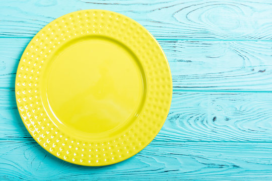 Empty yellow plate on wooden table