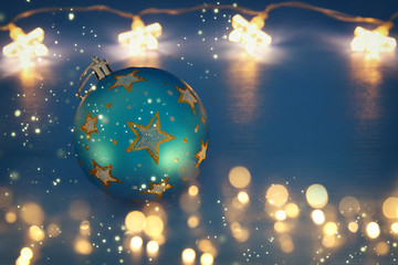 Image of christmas festive tree ball decoration with gold stars in front of blue background.