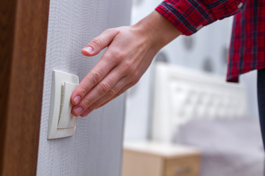 Hand on white wall switch. Turning the light off or on in the room
