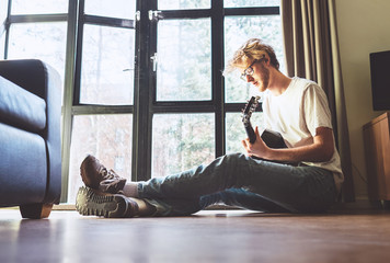 Middle shot of young man plays on guitar sitting on the floor in living room.
