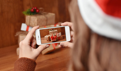 Woman with Santa's hat taking photo of pile of presents on wooden table with her phone