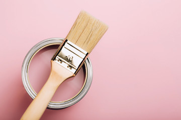 Brush with wooden handle on open can of pink paint on pastel background. Renovation concept. Macro.